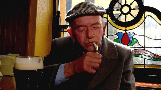 Ein älterer Herr mit karierter Schirmmütze und Sakko sitzt im Pub vor einem Bier und zündet sich eine Zigarette an.