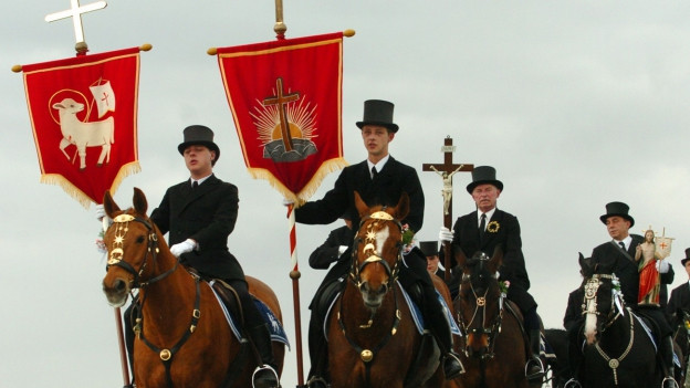 Männer zu Pferd in Trachten: es sind sorbische Osterreiter, sie tragen die Fahnen ihrer Kirchgemeinde an der Spitze der Prozession, nahe Panschwitz, 60 Kilometer oestlich von Dresden.