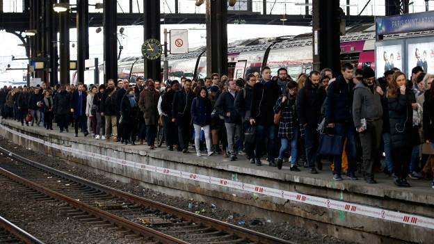Am Bahnsteig in Paris warten dutzende Menschen auf den Zug.