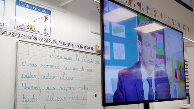 Der französische Präsident Emmanuel Macron erscheint im Fernsehen während des Interviews mit dem französischen Journalisten Jean-Pierre Pernaut im französischen Fernsehsender TF1 am 12. April 2018 in der Schule in Berdhuis westlich von Paris.