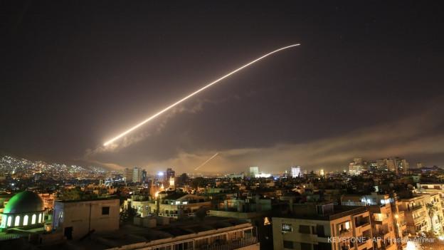 Über dem Nachthimmel von Damaskus leuchtet eine Rakete auf.