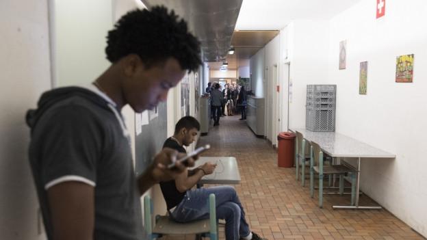 Zwei Asylsuchende blicken im Flur eines Asylzentrums auf ihre Handys.