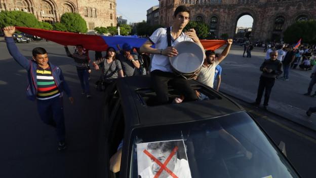 Auf dem Bild zu sehen sind Demonstranten mit Flagge und Musikinstrumenten in Jerewan