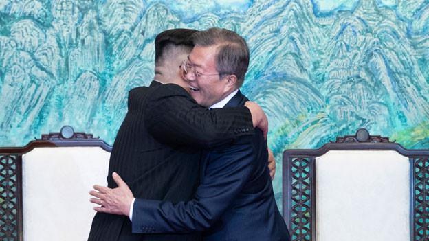 Der nordkoreanische Führer Kim Jong Un und der südkoreanische Präsident Moon Jae-in umarmen sich.