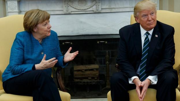 Angela Merkel spricht mit Donald Trump, er wendet sich leicht ab.