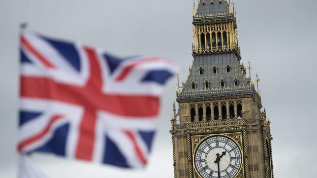 Der Big Ben in London. Davor die britische Flagge.