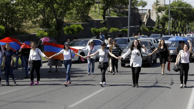 Menschen in Armenien laufen als eine Kette durch die Strassen.