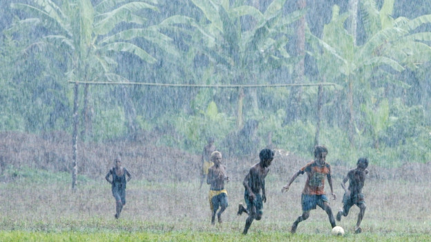 Zu sehen sind Kinder, die im Inselstaat Vanuatu im tropischen Regen Fussball spielen: Australien und China konkurrenzieren sich um politischen und wirtschaftlichen Einfluss im Südpazifik.