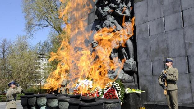 Polnischer Soldat salutiert vor Mahnmal, das an den jüdischen Aufstand im Warschauer Ghetto erinnert.
