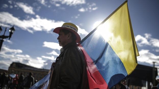 Ein Anhänger des linken Präsidentschaftskandidaten Gustavo Petro nimmt mit einer geschulterten kolumbianischen Flagge an einer Wahlveranstaltung in der Hauptstadt Bogota teil.e über d