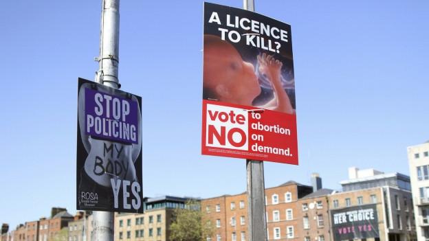 Das Bild zeigt Abstimmungsplakate für und gegen die Abtreibung.