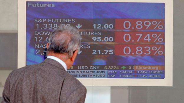 Ein Mann überprüft einen Börsenmonitor in Mailand, Italien.