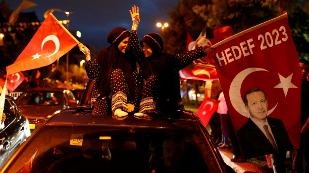 Zu sehen sind Anhänger von Präsident Erdogan, die vor der AKP-Zentrale in Istanbul überschwänglich den Wahlsieg feiern.