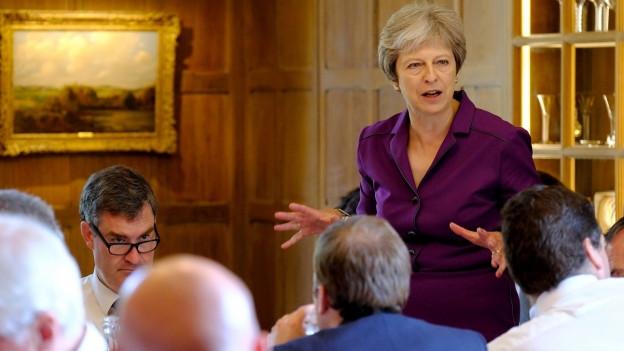 Teresa May spricht stehend zu ihren Ministern.