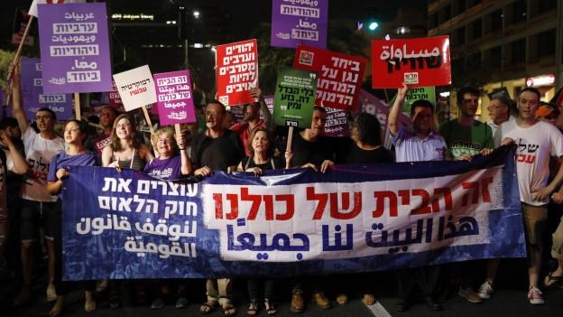 Protestierende auf den Strassen Tel Avivs halten farbige Plakate mit hebräischen Schriftzügen in die Kamera.
