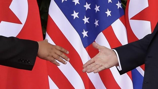 Kim Jong Un und Donald Trump geben sich die Hände.