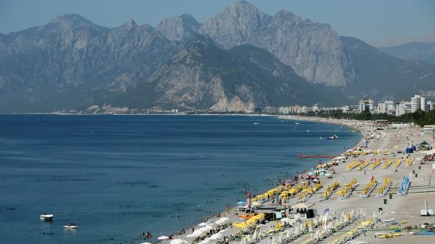 Touristen und Sonnenschirme an einem Strand in Antalya, im Hintergrund Berge