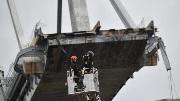 Helfer vor der eingestürzten Brücke in Genua.