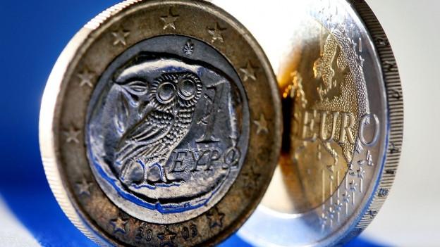 Euromünzen vor einer griechischen Flagge im Hintergrund