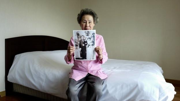 Hoffen auf das Treffen mit Verwandten in Nordkorea: eine Südkoreanerin mit einem Familienfoto.