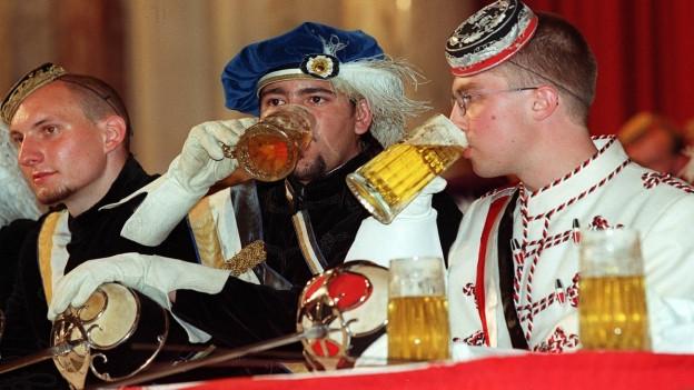 Drei Burschenschaftler mit Schärpen und Mützen an einer Veranstaltung in der Wiener Hofburg fröhnen dem Bier trinken.