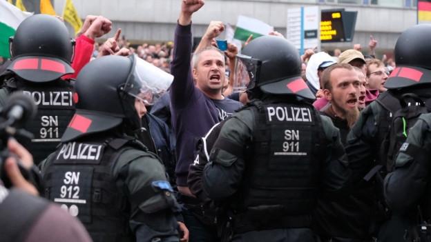 Demontranten stehen Polizisten gegenüber.