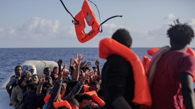 Flüchtlinge auf einem Schlauchboot erhalten Schwimmwesten.