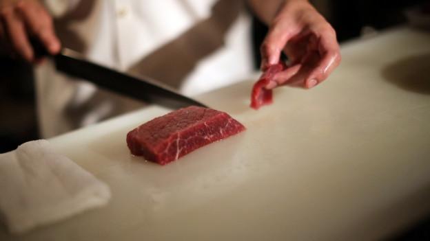 Person schneidet Walfleisch mit Messer.