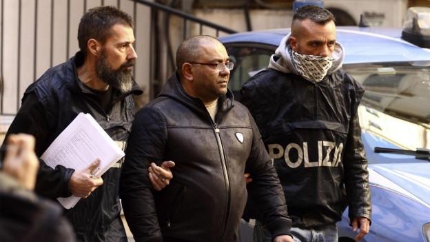 Zwei italienische Polizisten in Zivilkleidung führen einen mutmasslichen Mafiosi ab.