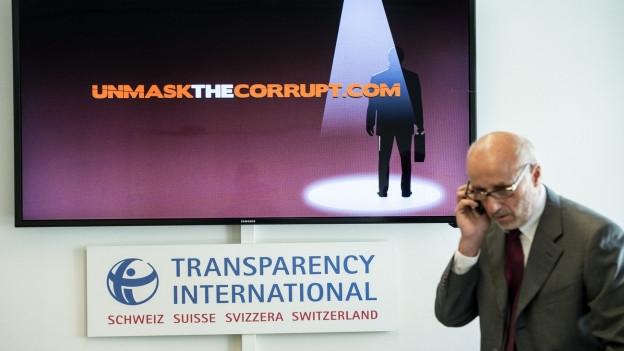 """Ein Mann telefoniert vor dem Plakat der Organisation """"Transparency International""""."""