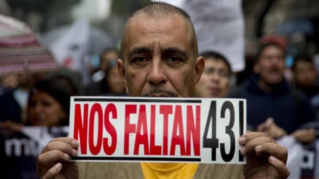 """Ein Mann trägt bei einer Demonstration ein Schild mit der spanischen Aufschrift """"Wir vermissen 43!""""."""
