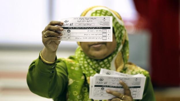 Eine Wählerin auf den Malediven schaut ihren Wahlzettel an.
