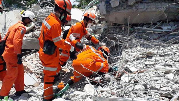 Helfer suchen nach Überlebenden.