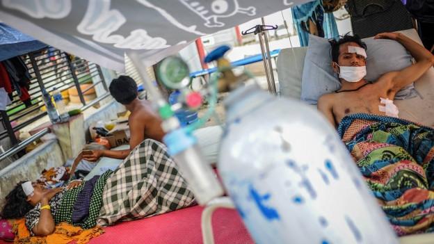 Verletzte Menschen liegen in einem Zelt.
