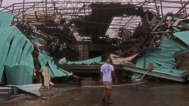 Ein Mann steht vor einem komplett zerstörten Gebäude.