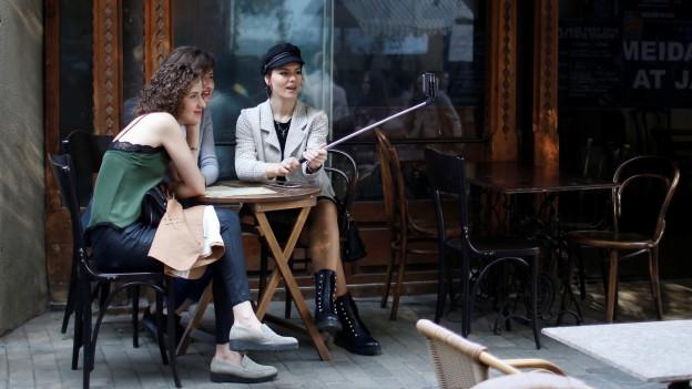 Junge georgische Frauen in einem Strassencafé machen ein Selfie von sich.