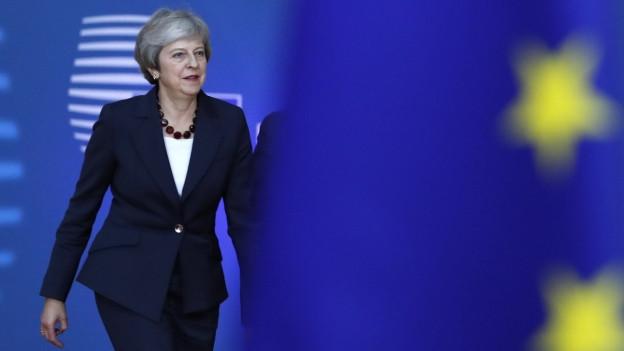 Das Bild zeigt die britische Premierministerin Theresa May neben einer Europaflagge am Rande des EU-Gipfels am 17. Oktober 2018.