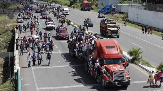 Menschen, die auf Autos steigen und versuchen durch Mexiko zu gelangen