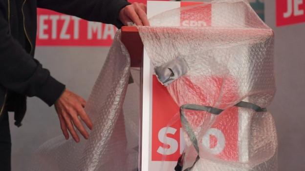 Das Rednerpult wird an der Wahlparty der hessischen SPD beim Abbau der Bühne mit Plastikfolie verpackt.