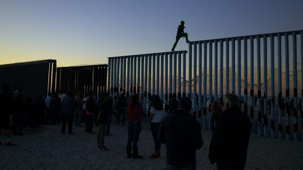 Lateinamerikanische Flüchtlinge versuchen einen Grenzzaun zu den USA zu überwinden.