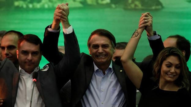 Jair Bolsonaro jubelt mit seinem Sohn und seiner Schwiegertochter.