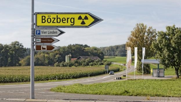 Digitalverändertes Bild: Gelber Wegweiser mit Nuklearzeichen versehen.