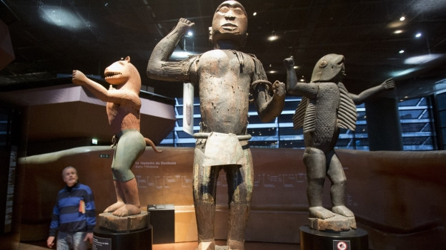 Holzstatuen von Gottheiten in einem Museum, ein Besucher betrachtet sie.