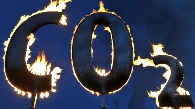 Symbolbild: Der mit Gas gespeiste Schriftzug «CO2» brennt am Kohlekraftwerk Staudinger in Hanau während einer Aktion der Umweltschutzorganisation Greenpeace Anfang 2018.
