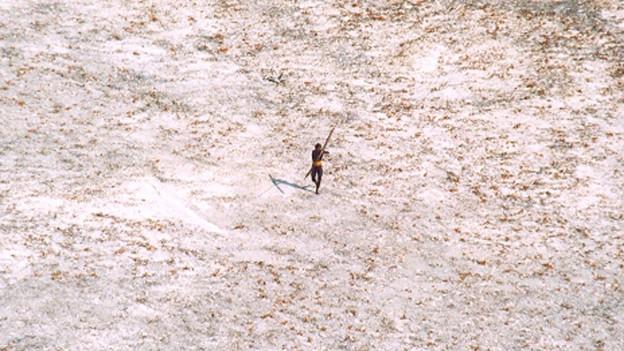Ein Bewohner vom Volk der Nord-Sentinelesen zielt mit Pfeil und Bogen von Weitem auf die Kamera.