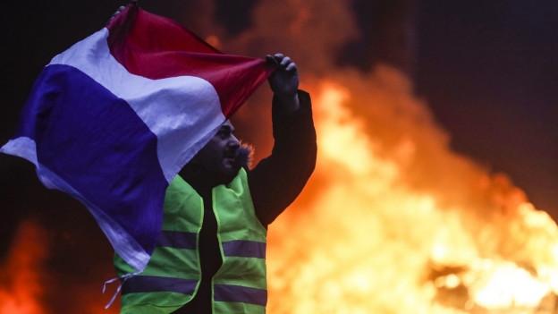Mann mit französischer Flagge vor Flammen