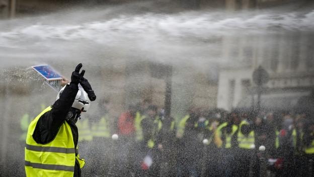 Ein Demonstrant hält seine Hände hoch, als die Polizei bei Protesten in Paris, Frankreich, die Situation entschärfen will.