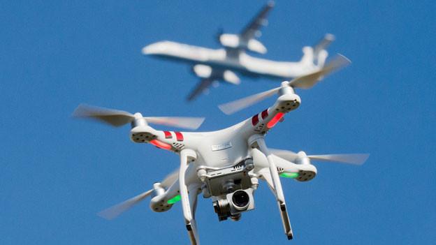 Eine Drohne unterhalb eines Flugzeuges.