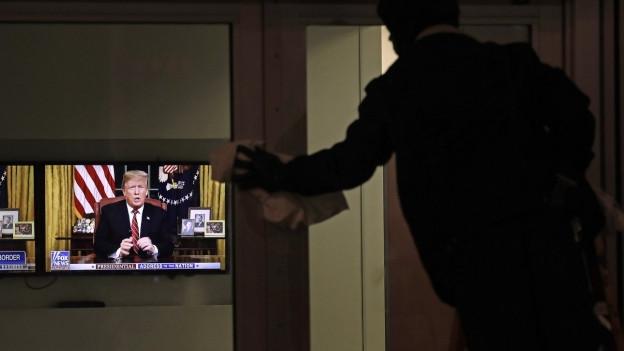 Ein Wartungsarbeiter putzt die Fenster. Im Hintergrund spricht US-Präsident Donald Trump im Fernsehen zu seiner Einwanderungspolitik