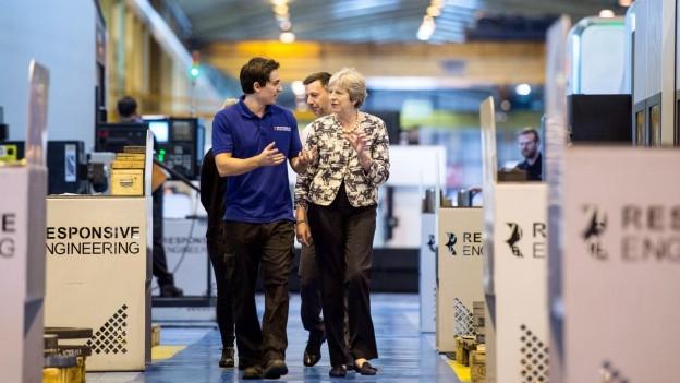 Auf dem Bild zu sehen ist die britische Premierministerin, die eine Firma besucht